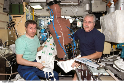 Cosmonaut and astronaut examine an experiment aboard the International Space Station.