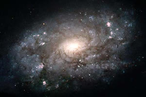 (Left) Hubble Space Telescope image of a spiral galaxy (NGC3949), about 50 million light years from Earth, located in the direction of the Big Dipper. Scientists think this galaxy is similar to our own in shape and structure, and they study it to get clues about the Milky Way. Like the Milky Way, there is a blue disk of young stars with bright pink areas where stars are believed to be born. The central bulge is made up of older, redder stars.