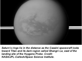 Saturn's rings lie in the distance as the Cassini spacecraft looks toward Titan and its dark region called Shangri-La, east of the landing site of the Huygens Probe. Credit:  NASA/JPL-Caltech/Space Science Institute.
