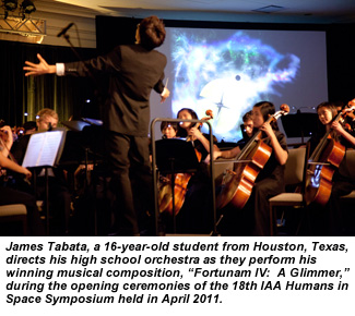James Tabata, a 16-year-old student from Houston, Texas, directs his high school orchestra as they perform his winning musical composition, Fortunam IV:  A Glimmer, during the opening ceremonies of the 18th IAA Humans in Space Symposium held in April 2011.