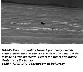 NASA's Mars Exploration Rover Opportunity used its panoramic camera to capture this view of a dark rock that may be an iron meteorite. Part of the rim of Endurance Crater is on the horizon. Credit:  NASA/JPL-Caltech/Cornell University.
