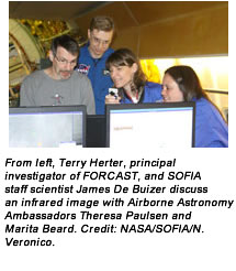 From left, Terry Herter, principal investigator of FORCAST, and SOFIA staff scientist James De Buizer discuss an infrared image with Airborne Astronomy Ambassadors Theresa Paulsen and Marita Beard. Credit: NASA/SOFIA/N. Veronico.