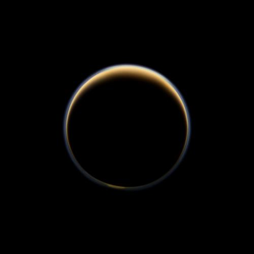 NASA's Cassini spacecraft looks toward the night side of Saturn's largest moon and sees sunlight scattering through the periphery of Titan's atmosphere and forming a ring of color. Image credit: NASA/JPL-Caltech/SSI.