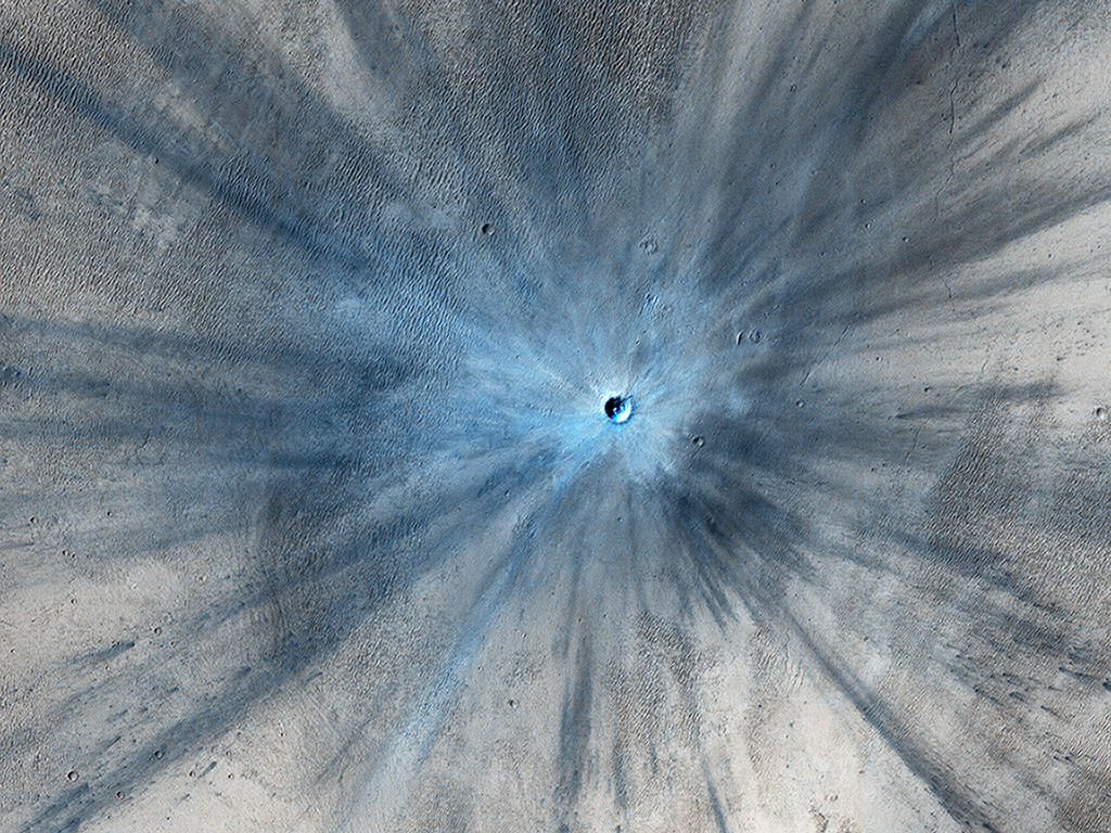 A dramatic, fresh impact crater dominates this image taken by the High Resolution Imaging Science Experiment (HiRISE) camera on NASA's Mars Reconnaissance Orbiter on Nov. 19, 2013.  Image Credit: NASA/JPL-Caltech/Univ. of Arizona.