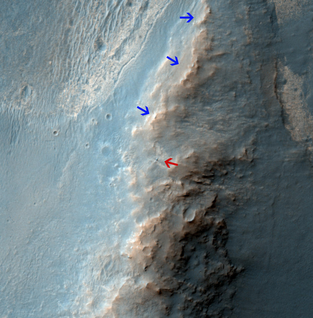 "The High Resolution Imaging Science Experiment (HiRISE) camera on NASA's Mars Reconnaissance Orbiter caught this view of NASA's Mars Exploration Rover Opportunity on Feb. 14, 2014. The red arrow points to Opportunity at the center of the image. Blue arrows point to tracks left by the rover since it entered the area seen here, in October 2013. The scene covers a patch of ground about one-quarter mile (about 400 meters) wide. North is toward the top. The location is the ""Murray Ridge"" section of the western rim of Endeavour Crater. Image Credit: NASA/JPL-Caltech/Univ. of Arizona."