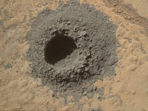 "NASA's Curiosity Mars rover completed a shallow ""mini drill"" test April 29, 2014, in preparation for full-depth drilling at a rock target called ""Windjana."" This image from Curiosity's Mars Hand Lens Imager shows the hole resulting from the test, 0.63 inch across and about 0.8 inch deep. Image Credit: NASA/JPL-Caltech/MSSS."