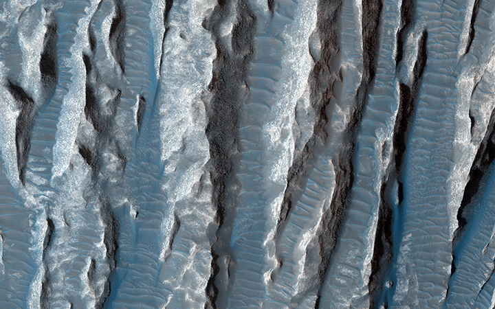 This view of Martian surface features shaped by effects of winds was captured by the HiRISE camera on NASA's Mars Reconnaissance Orbiter on Jan. 4, 2015. Image Credit: NASA/JPL-Caltech/Univ. of Arizona.