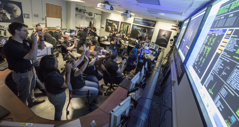 New Horizons Flight Controllers celebrate after they received confirmation from the spacecraft that it had successfully completed the flyby of Pluto, Tuesday, July 14, 2015 in the Mission Operations Center (MOC) of the Johns Hopkins University Applied Physics Laboratory (APL), Laurel, Maryland. Credits: NASA/Bill Ingalls.