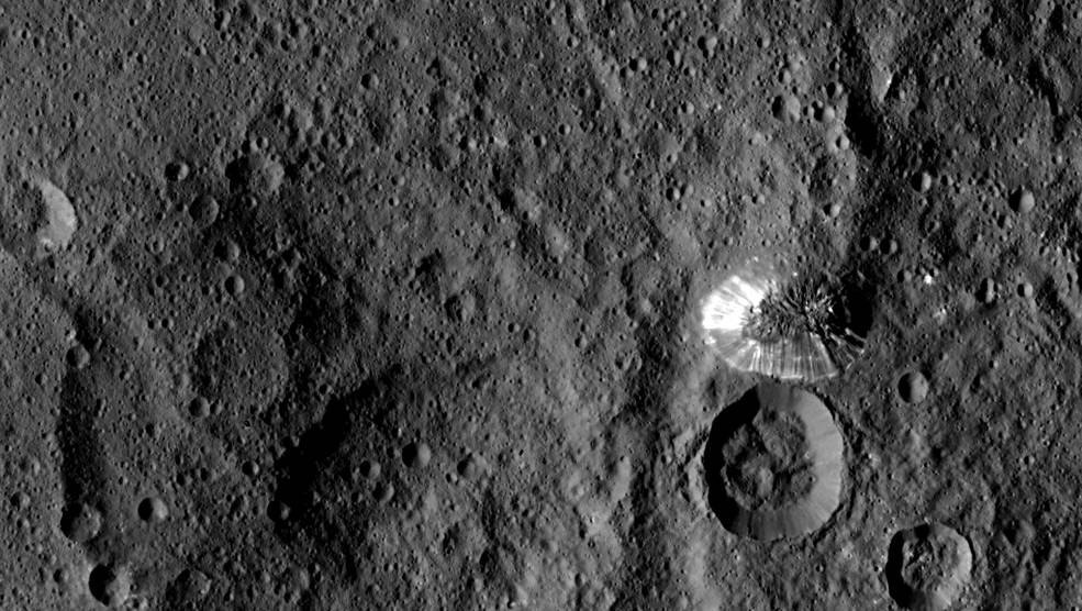 NASA's Dawn spacecraft spotted this tall, conical mountain on Ceres from a distance of 915 miles (1,470 kilometers). The mountain, located in the southern hemisphere, stands 4 miles (6 kilometers) high. Its perimeter is sharply defined, with almost no accumulated debris at the base of the brightly streaked slope with bright streaks. Credits: NASA/JPL-Caltech/UCLA/MPS/DLR/IDA.