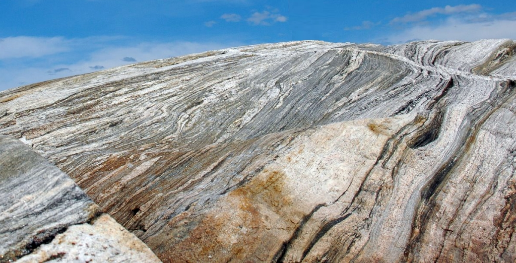 Gneiss exposed on the Canadian Shield. Hadean rocks of the Acasta Gneiss Complex in northwest Canada, similar in appearance to these ones, possibly formed as a result of large impacts on the early Earth more than 4 billion years ago, according to a new study. Image credit: Martin Schmieder/Lunar and Planetary Institute
